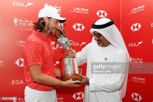 Tommy Fleetwood of England is presented the winner's trophy by Abdulfattah Sharaf CEO of HSBC in the UAE after the final round of the Abu Dhabi HSBC...