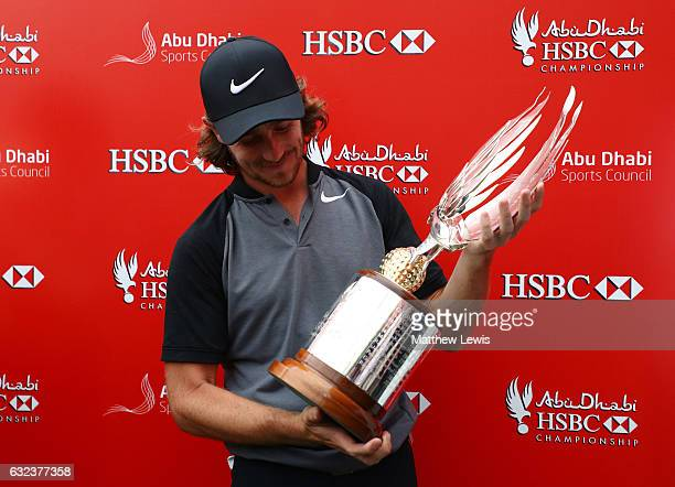 Tommy Fleetwood of England poses for photographs with the tropy after winning the tournament during the final round of the Abu Dhabi HSBC...