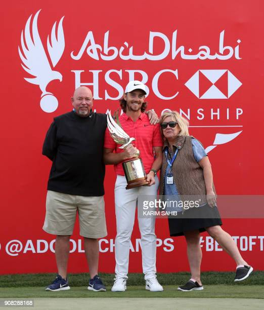 Tommy Fleetwood of England poses with his parents as he holds winner's trophy while celebrating his victory at the Abu Dhabi HSBC Golf Championship...