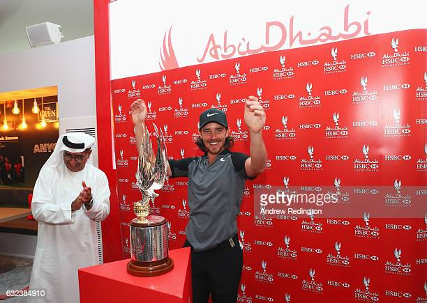 Tommy Fleetwood of England poses with the trophy and Abdulfattah Sharaf after winning the tournament during the final round of the Abu Dhabi HSBC...