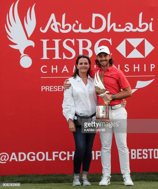 Tommy Fleetwood of England poses with the winner's trophy as he embraces his spouse Clare Craig while celebrating his victory at the Abu Dhabi HSBC...