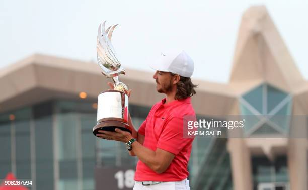 Tommy Fleetwood of England poses with the winner's trophy while celebrating his victory at the Abu Dhabi HSBC Golf Championship at the Abu Dhabi Golf...