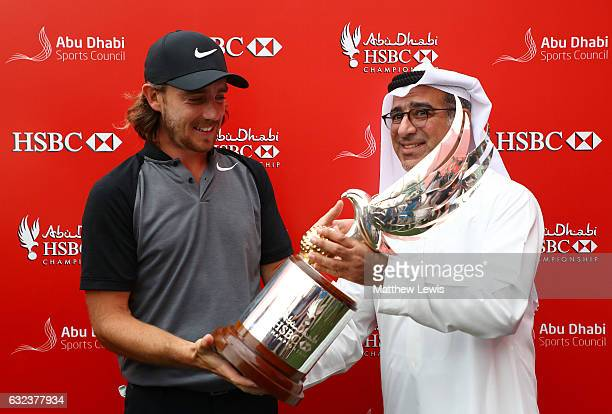 Tommy Fleetwood of England receives the trophy from Abdulfattah Sharaf after winning the tournament during the final round of the Abu Dhabi HSBC...