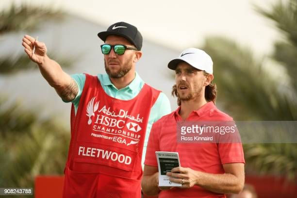 Tommy Fleetwood of England talks with his caddie Ian Finnis on the 18th tee during the final round of the Abu Dhabi HSBC Golf Championship at Abu...
