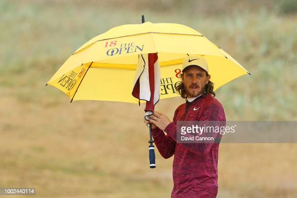 Tommy Fleetwood of England waits to hit his second shot on the 18th hole using an official Open Championship umbrella that his caddie bought from the...