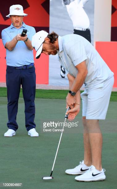 Tommy Fleetwood of England works on his putting with putting coach Phil Kenyon of England as a preview for the Omega Dubai Desert Classic at Emirates...
