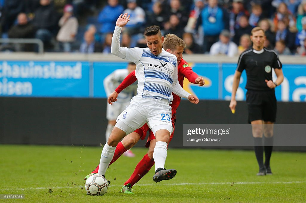 Tommy Grupe of Rostock (back) tackles Fabian Schnellhardt of Duisburg during the third league match between MSV Duisburg and Hansa Rostock at Schauinsland-Reisen-Arena on October 22, 2016 in Duisburg, Germany.