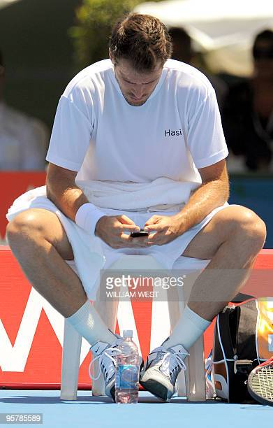 Tommy Haas of Germany uses his mobile phone during a break in his loss to JoWilfried Tsonga of France at the Kooyong Classic tennis tournament in...