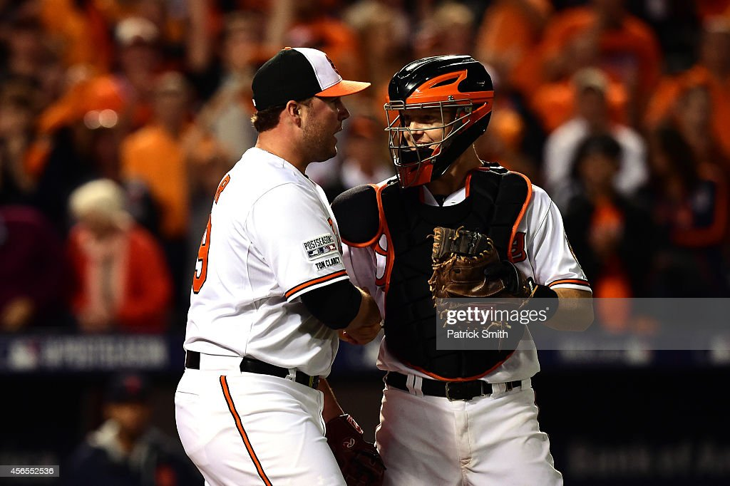 Tommy Hunter #29 of the Baltimore Orioles talks with Nick Hundley #40 after defeating the Detroit Tigers 12-3 in Game One of the American League Division Series at Oriole Park at Camden Yards on October 2, 2014 in Baltimore, Maryland.