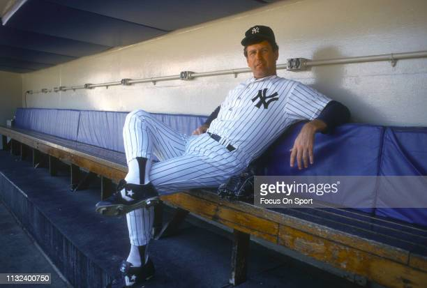 Tommy John of the New York Yankees looks on from the dugout prior to the start of a Major League Baseball game circa 1987 at Yankee Stadium in the...