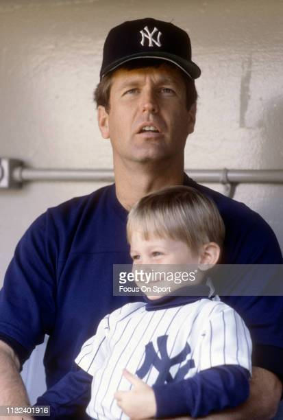 Tommy John of the New York Yankees looks on from the dugout while sitting with his son prior to the start of a Major League Baseball game circa 1980...