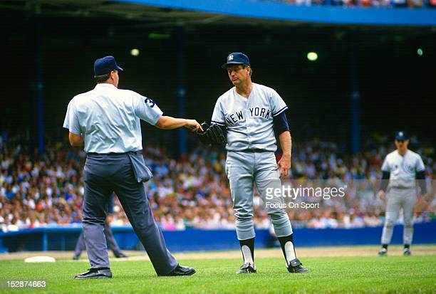 Tommy John of the New York Yankees takes a ball from the home plate umpire during an Major League Baseball game circa 1982 John played for the...