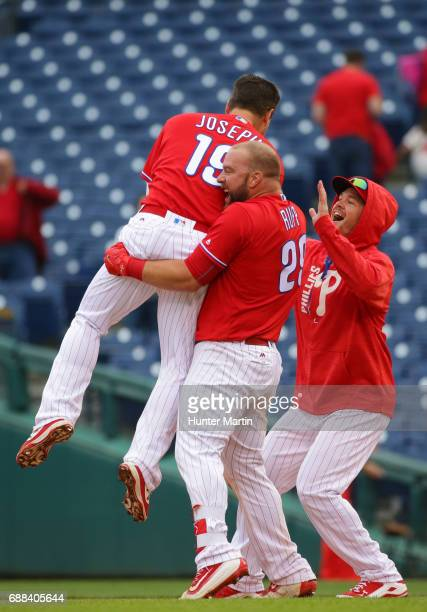 Tommy Joseph of the Philadelphia Phillies is picked up by Cameron Rupp after hitting a game winning walkoff RBI single in the 11th inning during a...