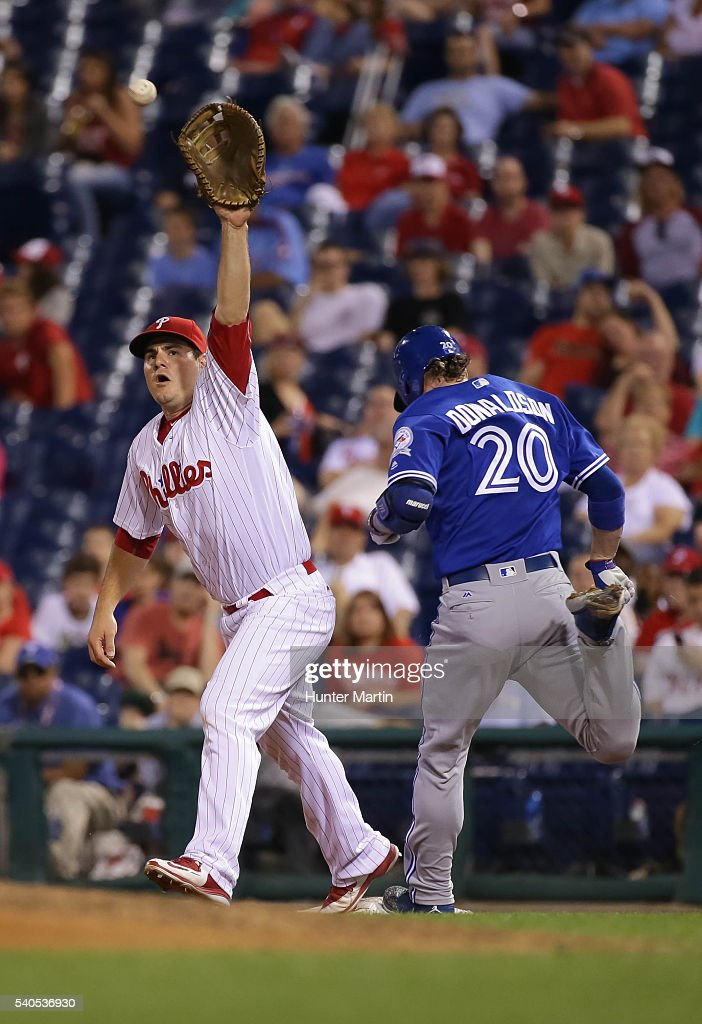 Tommy Joseph #19 of the Philadelphia Phillies reaches to catch a throw as Josh Donaldson #20 of the Toronto Blue Jays is called safe at first on an infield single in the ninth inning during a game against the Toronto Blue Jays at Citizens Bank Park on June 15, 2016 in Philadelphia, Pennsylvania. The Blue Jays won 7-2.