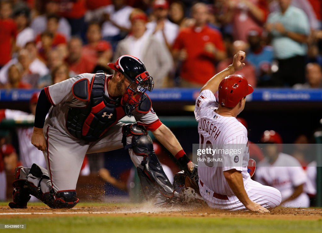 Tommy Joseph #19 of the Philadelphia Phillies scores past the tag of catcher Matt Wieters #32 of the Washington Nationals on a two-run double by Cameron Rupp #29 during the third inning of a game at Citizens Bank Park on September 26, 2017 in Philadelphia, Pennsylvania.