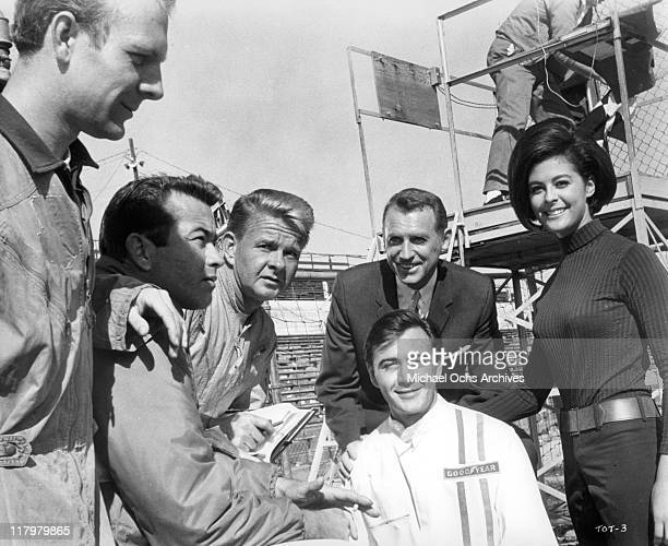 Tommy Kirk a top racing driver surrounded by Ray Stricklyn James Dobson Chet Stratton and Brenda Benet in a scene from the film 'Track of Thunder'...