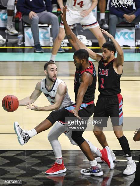 Tommy Kuhse of the Saint Mary's Gaels passes against Parker Dortch and Joe Quintana of the Loyola Marymount Lions>> during the West Coast Conference...