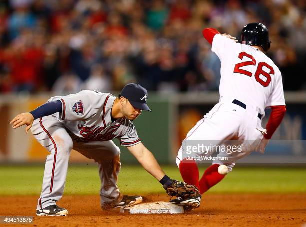 Tommy La Stella of the Atlanta Braves misses catching the throw at second base in front of Brock Holt of the Boston Red Sox that allowed the...