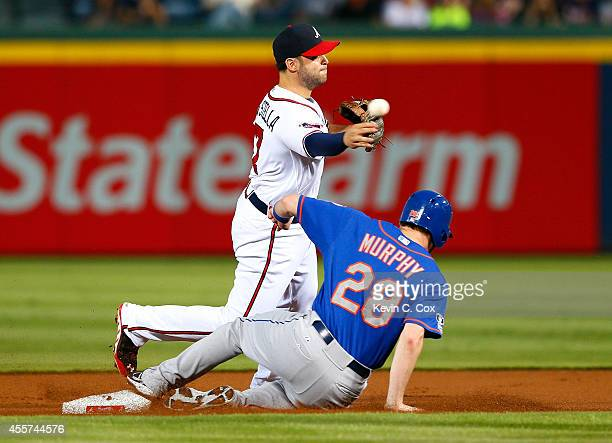Tommy La Stella of the Atlanta Braves turns a double play over Daniel Murphy of the New York Mets in the first inning at Turner Field on September...