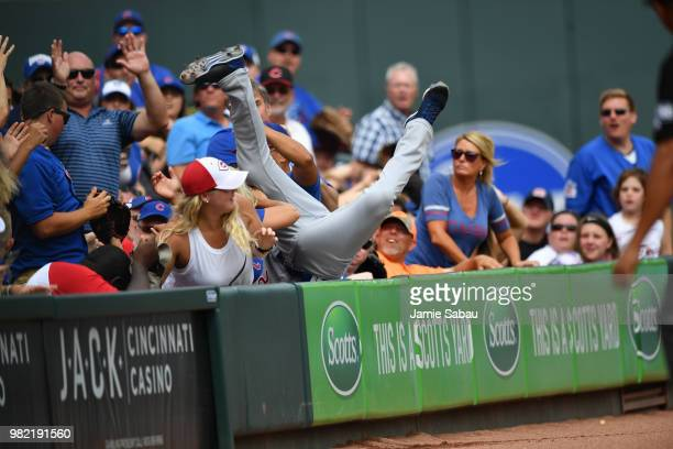 Tommy La Stella of the Chicago Cubs goes head over heals into the crowd as he makes the catch of a fly ball in the first inning against the Chicago...