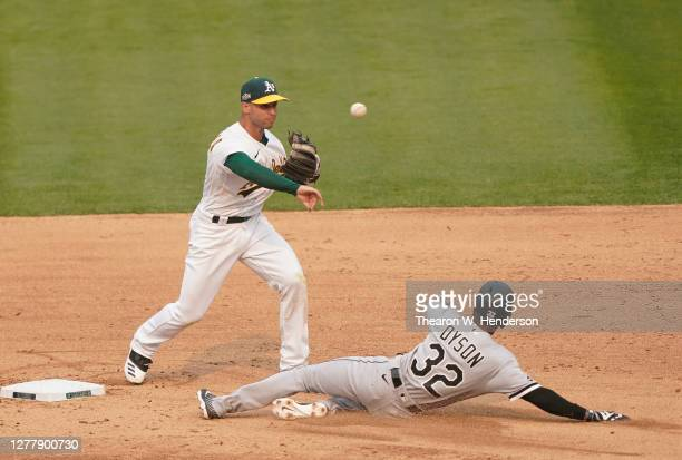 Tommy La Stella of the Oakland Athletics completes the double-play throwing over the top of Jarrod Dyson of the Chicago White Sox during the eighth...