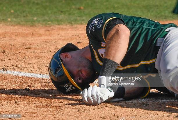 Tommy La Stella of the Oakland Athletics reacts after being hit by a pitch by Brooks Raley of the Houston Astros during the eighth inning in Game...