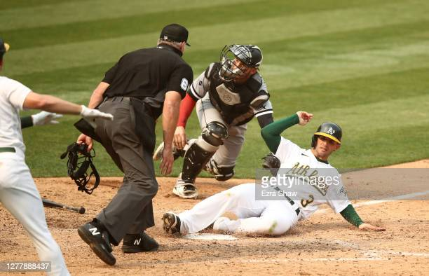 Tommy La Stella of the Oakland Athletics slides past Yasmani Grandal of the Chicago White Sox to score in the fifth inning of Game Three of the...