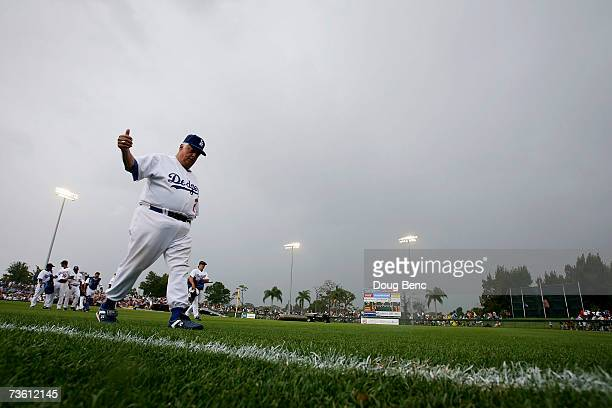 Tommy Lasorda of the Los Angeles Dodgers gives fans a thumbs up as he leaves the field when the rain canceled the game against the Boston Red Sox...