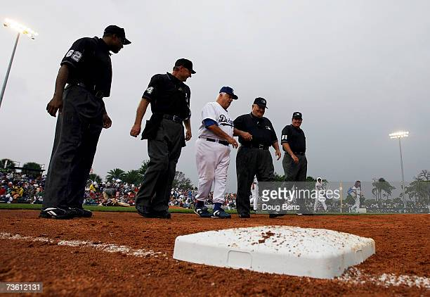 Tommy Lasorda of the Los Angeles Dodgers makes his way off the field with the four umpires after the rain canceled the game against the Boston Red...