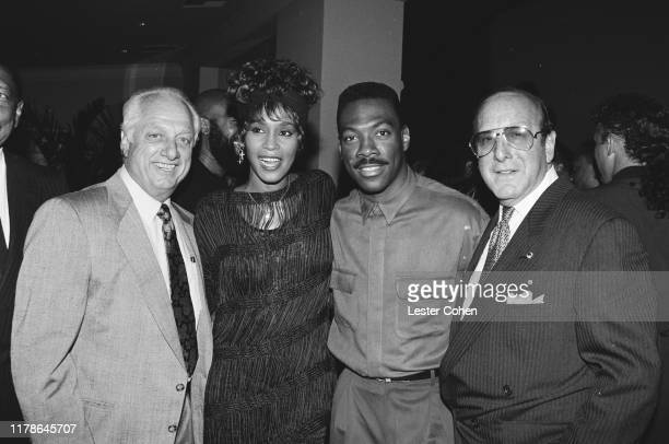 Tommy Lasorda Whitney Houston Eddie Murphy and Clive Davis attend a party in Los Angeles California circa 1988