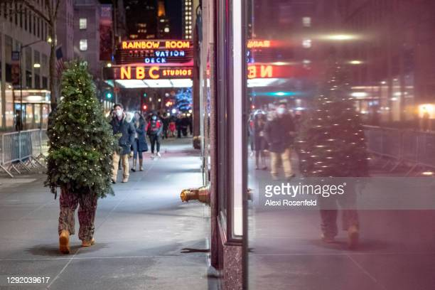Tommy Liberto, aka Mr. Christmas Tree, visiting from Bel Air, Maryland, casts a refelction onto a wall near NBC Studios at Rockefeller Center on...