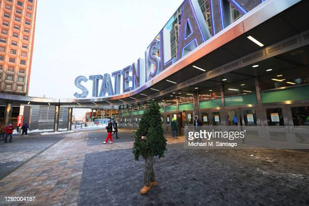 Tommy Liberto walks out of the Staten Island ferry terminal after arriving in NYC wearing a Christmas tree costume on December 18, 2020 in New York...