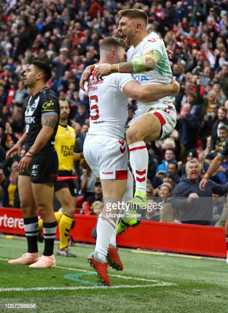 Tommy Makinson of England celebrates with teammate George Williams after scoring a try during the International Series second test match between...