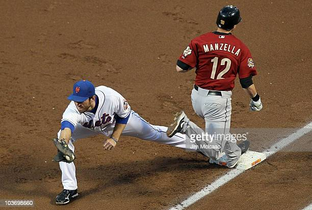Tommy Manzella of the Houston Astros is safe at first base ahead of the force from Ike Davis of the New York Mets allowing a run to score from third...