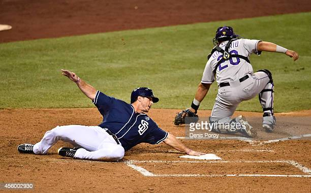 Tommy Medica of the San Diego Padres scores ahead of the throw to Wilin Rosario of the Colorado Rockies during the sixth inning of a baseball game at...
