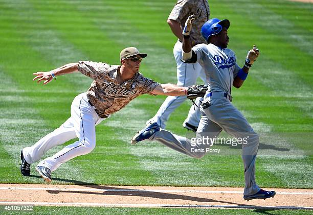 Tommy Medica of the San Diego Padres tags out Dee Gordon of the Los Angeles Dodgers on the first base line during the seventh inning of a baseball...