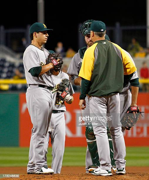 Tommy Milone of the Oakland Athletics talks with pitching coach Curt Young of the Oakland Athletics during the game against the Pittsburgh Pirates on...