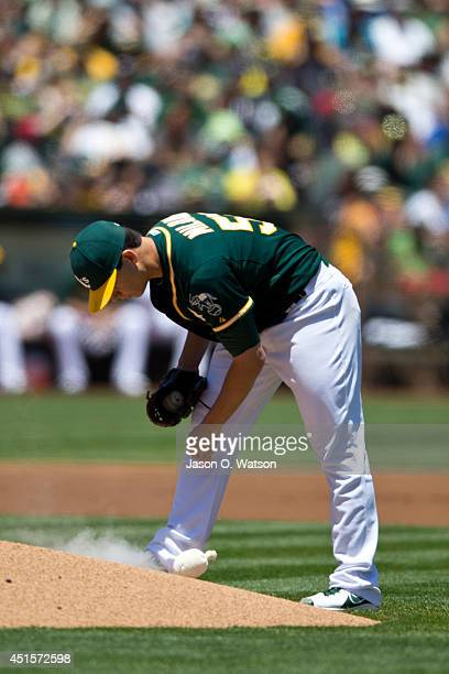 Tommy Milone of the Oakland Athletics throws a bag of chalk behind the pitchers mound after walking Mike Napoli of the Boston Red Sox during the...