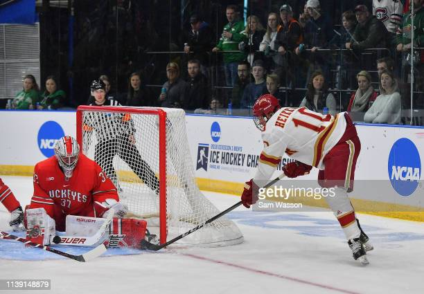 Tommy Nappier of the Ohio State Buckeyes stops a shot from Jaakko Heikkinen of the Denver Pioneers during an NCAA Division I Men's Ice Hockey West...