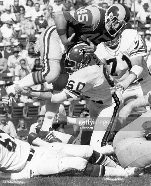 Tommy Nobis of the Atlanta Falcons tackles Jim Bertelsen of the Los Angeles Rams during an NFL game.