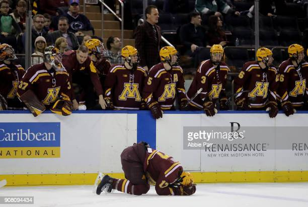 Tommy Novak of the Minnesota Golden Gophers lays on the ground after injuring himself against a Michigan State Spartans player during their game at...