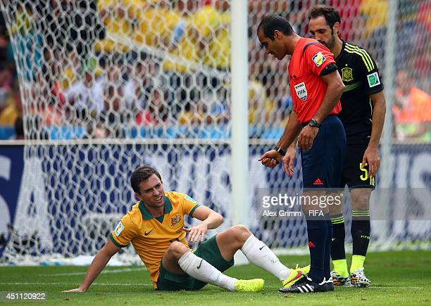 Tommy Oar of Australia sits on the field as referee Nawaf Shukralla looks on during the 2014 FIFA World Cup Brazil Group B match between Australia...