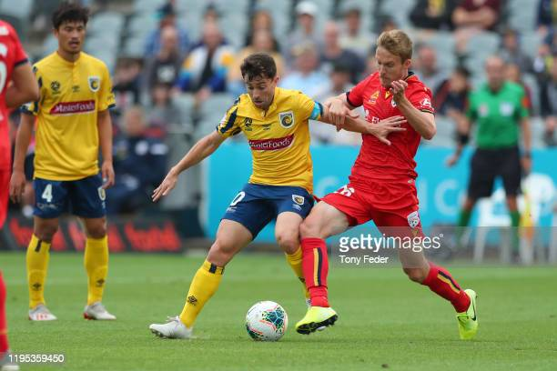 Tommy Oar of the Central Coast Mariners contests the ball with Ben Halloran of Adelaide United during the round 11 ALeague match between the Central...