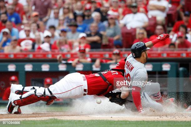 Tommy Pham of the St Louis Cardinals scores on a sacrifice fly in the third inning ahead of the tag by Tucker Barnhart of the Cincinnati Reds at...
