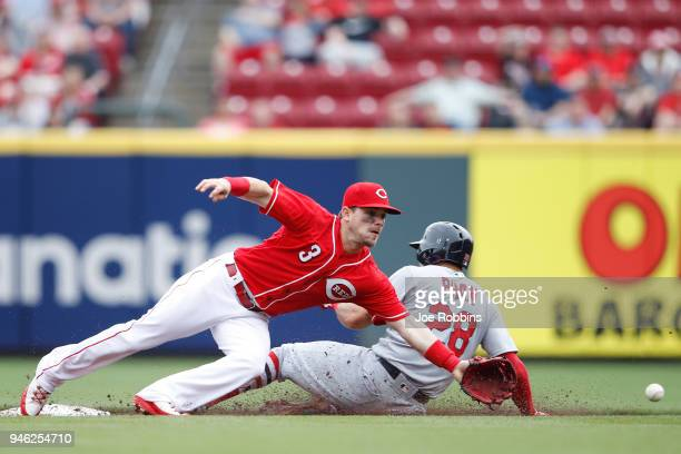 Tommy Pham of the St Louis Cardinals steals second base ahead of a bad throw to Scooter Gennett of the Cincinnati Reds in the third inning of the...
