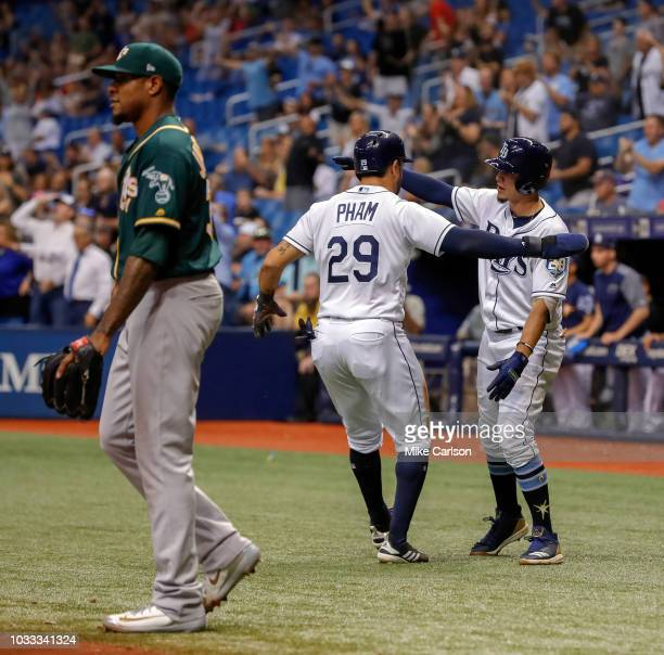 Tommy Pham of the Tampa Bay Rays is congratulated by Willy Adames after scoring in front of Edwin Jackson of the Oakland Athletics in the fourth...