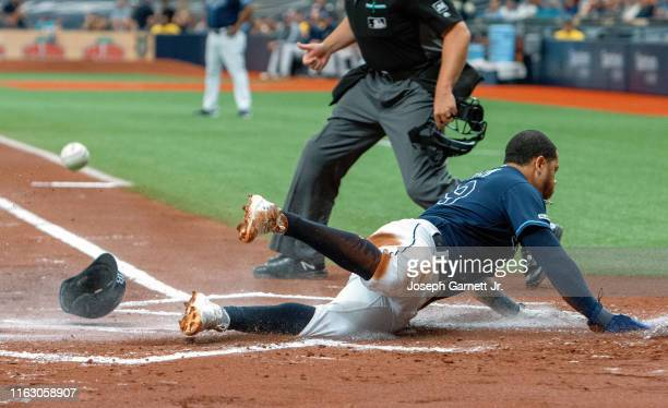 Tommy Pham of the Tampa Bay Rays slides across home plate for the team's first score during the bottom of the first inning of their game against the...