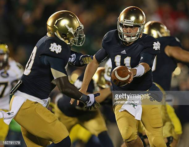 Tommy Rees of the Notre Dame Fighting Irish hands off to Cierre Wood against the Michigan Wolverines at Notre Dame Stadium on September 22 2012 in...