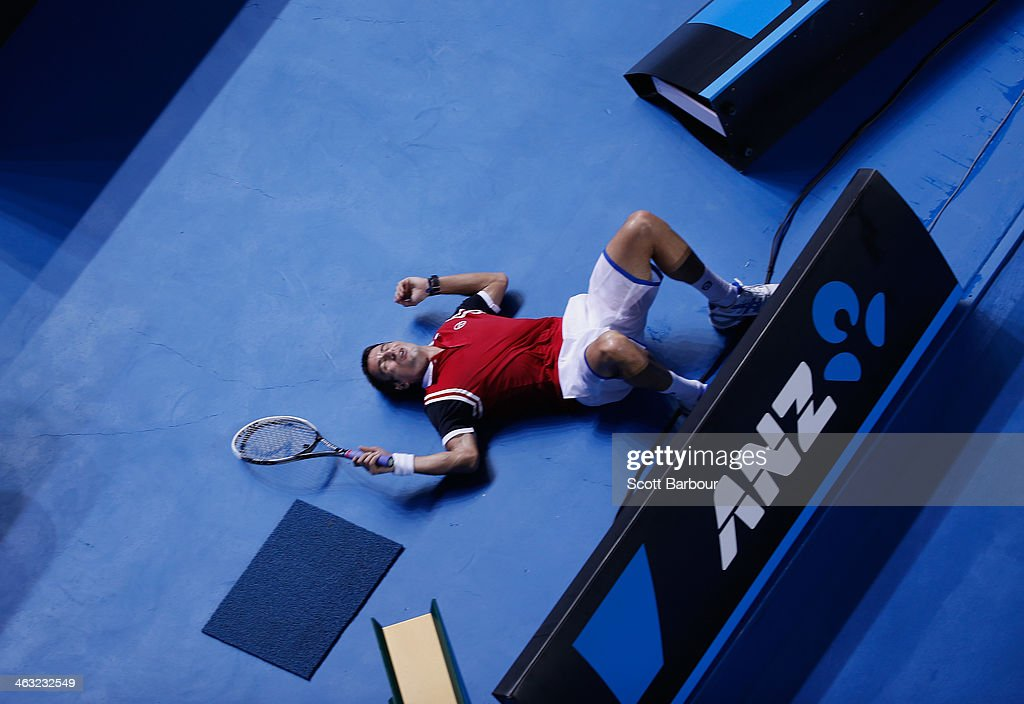 Tommy Robredo of Spain lies on the ground after tripping over the advertising hoardings on the court during his third round match against Richard Gasquet of France during day five of the 2014 Australian Open at Melbourne Park on January 17, 2014 in Melbourne, Australia.