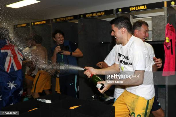 Tommy Rogic of Australia sprays champagne as Australia celebrate victory during the 2018 FIFA World Cup Qualifiers Leg 2 match between the Australian...